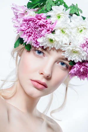 Portrait of a sensual spring lady in a wreath of flowers. Beauty, cosmetics. Make-up. White background.