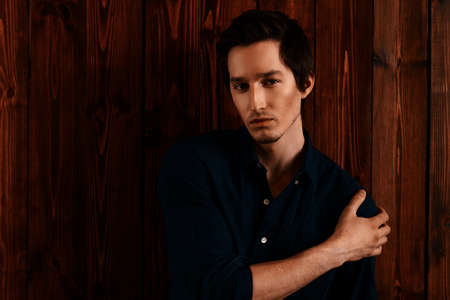 Vogue shot of a handsome male model in a denim shirt standing by a wooden wall. Mens beauty, fashion.