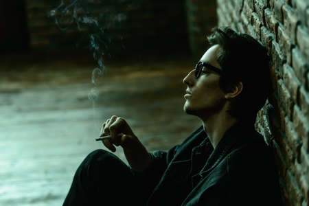 Attractive young man thoughtfully and calmly smoking a cigarette. Loft style interior. Mens beauty, fashion. Optics style.