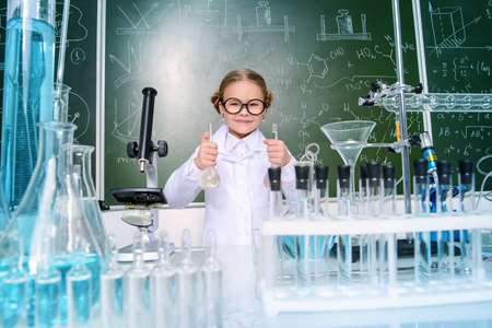 Little girl scientist doing chemical experiments in the laboratory. Science and education.