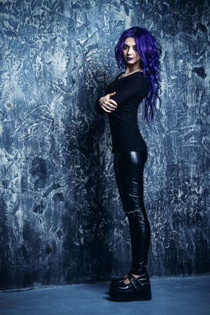 Attractive young woman with purple hair dressed in a black sweatshirt leather pants and platform shoes. Beauty, youth fashion. Hair coloring. Cosmetics, make-up.