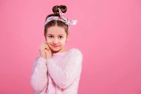 Children's fashion. Cute seven year old girl wearing pink cardigan posing over pink background. Studio shot.  版權商用圖片
