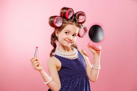 Portrait of a pretty little girl with curlers in her hair holding lipstick and mirror. Studio shot over pink background. Kids fashion.  写真素材