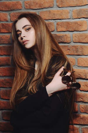 Modern teen girl posing by a brick wall. Urban youth style. Adolescence, transition problems.