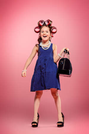 Portrait of a funny little girl with curlers in her hair in mother's shoes and bag. Studio shot over pink background. Kid's fashion.
