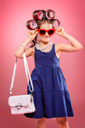Portrait of a pretty little girl with curlers in her hair holding a bag. Studio shot over pink background. Kids fashion.