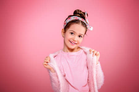 Children's fashion. Cute seven year old girl wearing pink cardigan posing over pink background. Studio shot.  Фото со стока