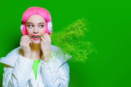 Trendy vivid girl with pink hair wearing headphones holding a bunch of grass. Green background. Beauty, fashion, youth style.