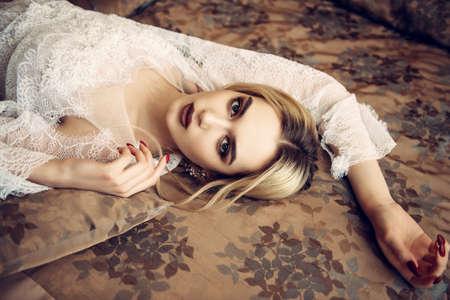 Wspaniała młoda kobieta pozowanie w sypialni ubrana w białą suknię wieczorową lub ślubną. Piękno, moda.