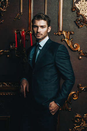 Imposing well dressed man in a luxurious apartments with classic interior. Luxury. Men's beauty, fashion. Reklamní fotografie - 100208124