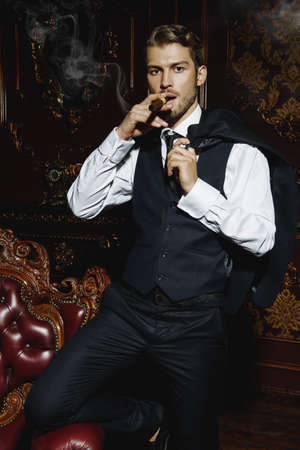 Imposing well dressed man in a luxurious apartments with classic interior smoking a cigar. Luxury. Mens beauty, fashion.