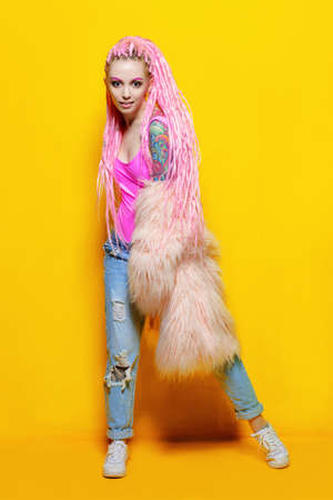 Stylish girl with pink dreadlocks posing in bright clothes on a yellow background. Full length portrait. Beauty, fashion.