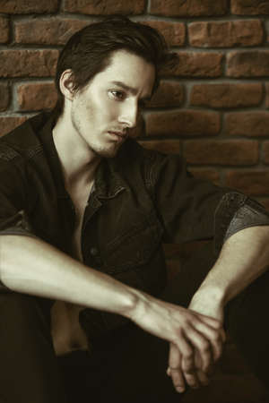 Male beauty, fashion. Handsome young man posing in black denim jacket by the brick wall. Hair styling.