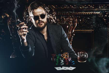 Ein reicher reifer Mann, der Zigarre raucht und in einem Kasino Poker spielt. Glücksspiel, Karten spielen und Roulette.