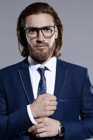 Fashion shot. Handsome spectacled young man posing in elegant blue suit and white shirt. Mens beauty, fashion. Style optics. Stok Fotoğraf