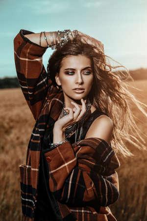 Fashion female model posing in a field. Contemporary bohemian style. Stockfoto