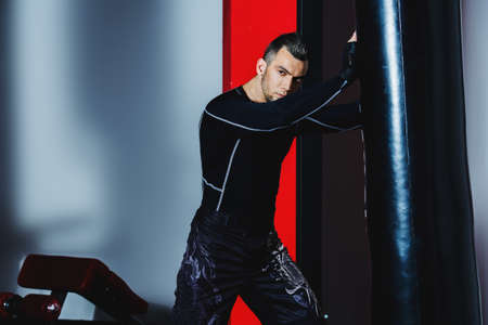 Portrait of a handsome athletic man training blows on a punching bag in the gym. Healthy lifestyle. Stock Photo