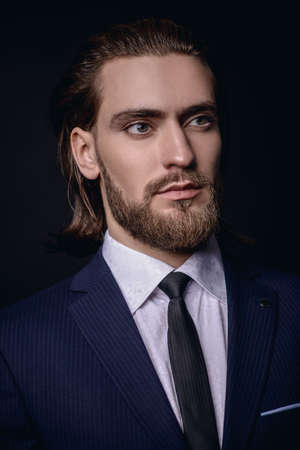 Fashion shot. Handsome young man posing in elegant suit and white shirt over black background. Mens beauty, fashion.