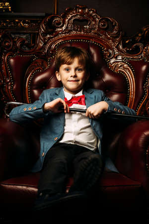 Handsome seven year old boy in elegant suit posing in luxurious apartments. Kid's fashion.