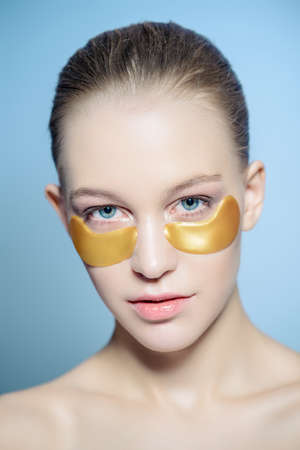 Close-up portrait of a beautiful young woman with collagen pads under her eyes. Spa, eye skin care. Foto de archivo - 100700197