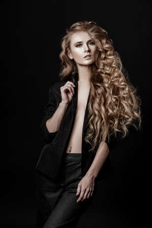 Portrait of a girl with long curly hair on a black background. Beauty, fashion.