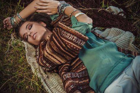 Beautiful hippie girl lying in a grass. Modern boho style. Beauty, fashion,