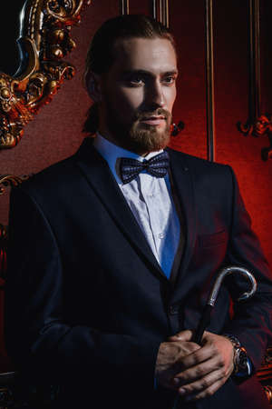 Portrait of a well-dressed imposing man in elegant suit posing in apartments with luxurious classic interior. Mens beauty, fashion. Hair styling, barbershop.  Imagens