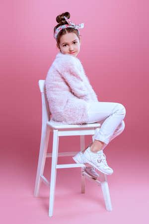 Childrens fashion. Cheerful seven year old girl wearing pink cardigan posing over pink background. Studio shot.  Stockfoto