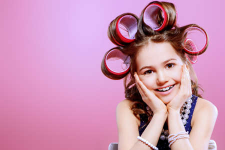 Porträt eines hübschen kleinen Mädchens mit Lockenwicklern im Haar. Studio schoss über rosa Hintergrund. Kindermode.
