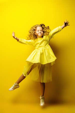 Moda infantil. Hermosa niña en vestido amarillo saltando en el estudio sobre fondo amarillo. Foto de archivo
