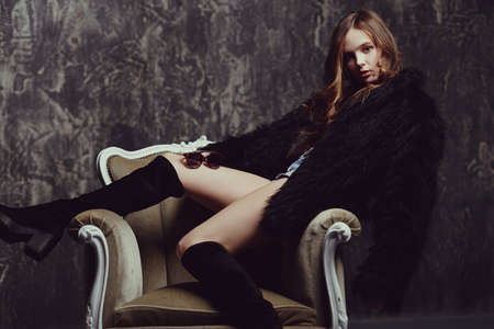 Attractive young woman posing in an armchair in a black fur coat and long boots. Beauty, fashion.  스톡 콘텐츠