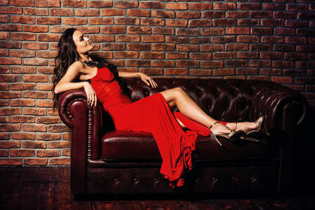 Gorgeous attractive woman in a beautiful red dress is sitting on a leather couch in a luxury apartment. Beauty, fashion. Stok Fotoğraf