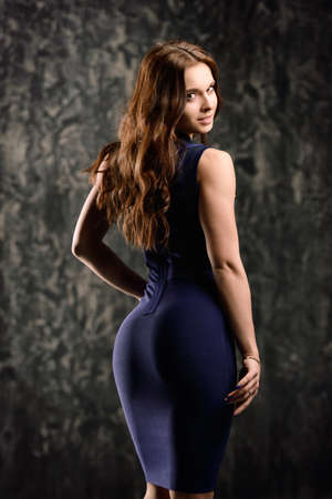 Young woman with a beautiful figure posing in a blue tight dress over grunge background.