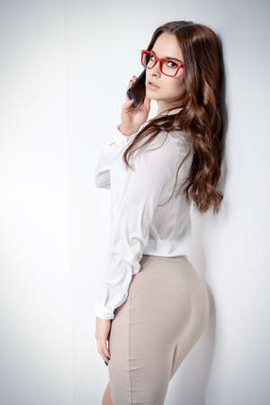 Attractive young woman posing in elegant clothes in a studio. Fashion, business style. 写真素材