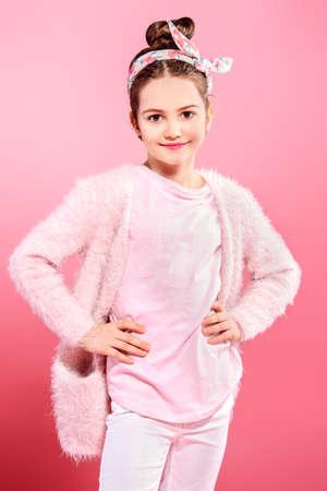 Children's fashion. Cheerful seven year old girl wearing pink cardigan posing over pink background. Studio shot.