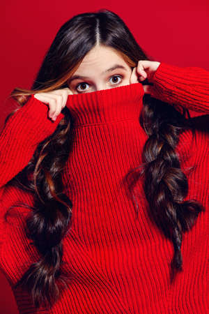 Teen style. Beautiful female model with long hair posing at studio in red jersey. Red background. Beauty, fashion.