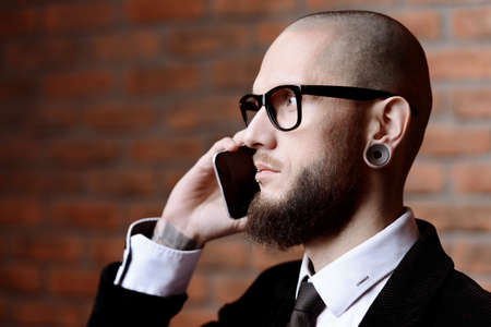 Close-up portrait of a businessman in elegant classic suit and piercing in the ears and lips talking on the phone. Mens beauty, fashion.