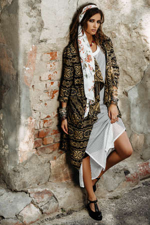 Female style. Feminine fashion model posing in boho style clothes on a street. Outdoor fashion. Banco de Imagens