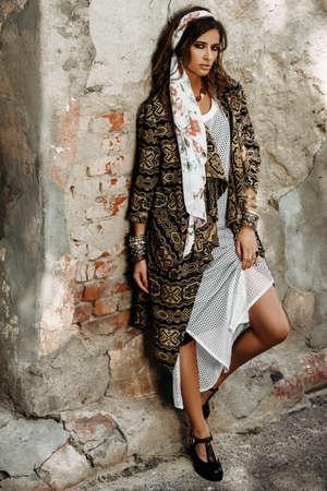 Vrouwelijke stijl. Vrouwelijke mannequin poseren in boho-stijl kleding op een straat. Outdoor mode.