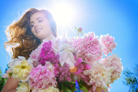 Portrait of a beautiful young woman with a bouquet of fresh summer flowers outdoor. Beauty, cosmetics. Summer vacation.