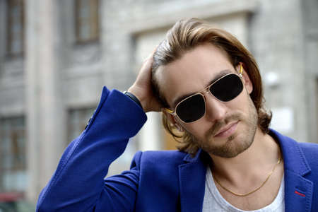 Handsome young man in sunglasses on a city street. Mens beauty, fashion. Active lifestyle. Stockfoto