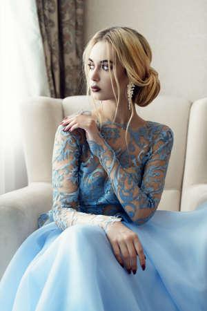 Ritratto di una giovane e bella donna in un elegante abito blu. Appartamenti lussuosi.