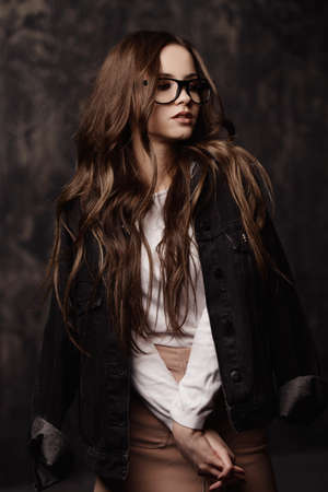Portrait of a attractive young woman in modern youth clothes and glasses. Studio shot over dark background. Beauty, fashion concept.