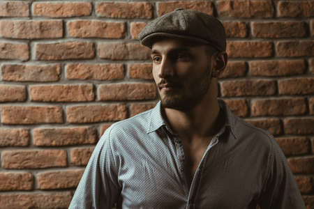 Portrait of a handsome brunet man in a cap over brick wall background. Mens beauty, fashion. Mens barbershop.