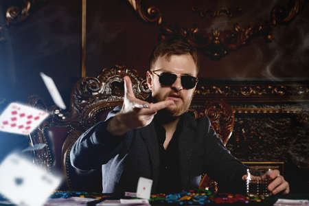 A wealthy mature man drinking whiskey and playing poker with the excitement in a casino. Gambling, playing cards and roulette.
