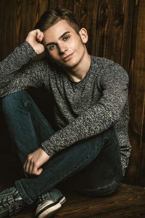 Portrait of a handsome teenage boy over wooden background. Studio shot. Teen fashion.