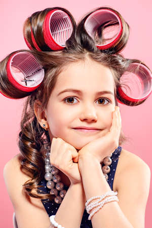 Portrait of a pretty little girl with curlers in her hair. Studio shot over pink background. Kid's fashion.  写真素材