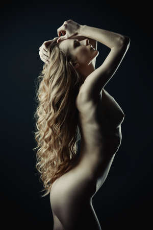 Nude girl posing on a black background. Female silhouette. Young woman with long curly hair.