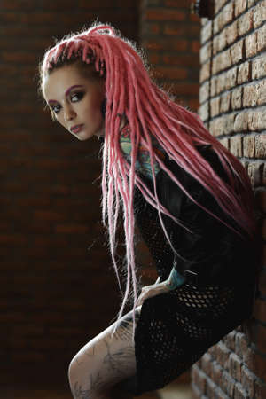 Sexy hipster girl with pink dreadlocks posing by the brick wall. Beauty, fashion. 写真素材