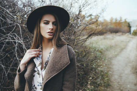 Autumn mood. Beautiful young woman  in autumn clothes posing outdoor.  Seasonal autumn fashion.